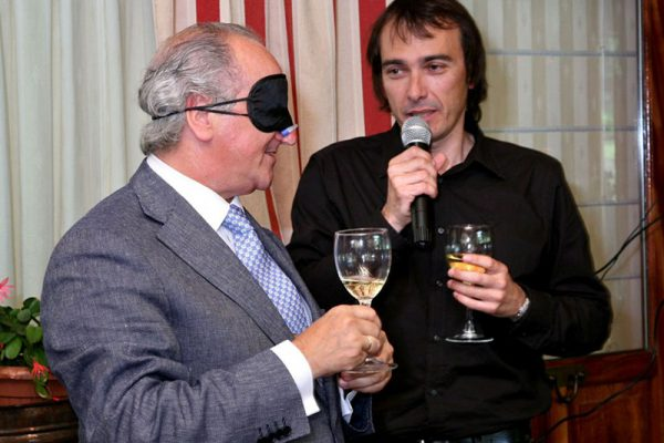 Blindfolded man tasting his wine in Calling the Shots