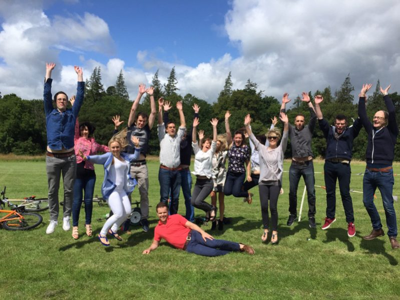 Team jumping with their hands in the air after they have completed their outdoor team building activities with Orangeworks.