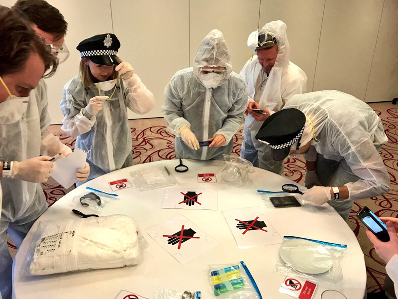 Delegates wearing white overalls taking pictures and examining evidence found during their team bonding activity.