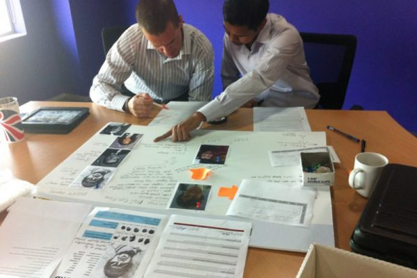 Team creating a suspect sheet in CSI, a crime style team building activity hosted by Orangeworks.