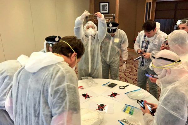 Crime Scene detectives in white suits taking pictures of evidence during the team bonding exercise hosted by Orangeworks.