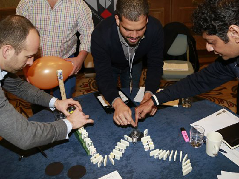 Delegates setting up their domino sequence during Domino Effect, an indoor team building activity hosted by Orangeworks.