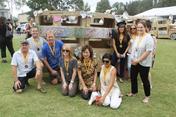 Winning team wearing medals smiling with their cardboard bus they built during the corporate team experience.