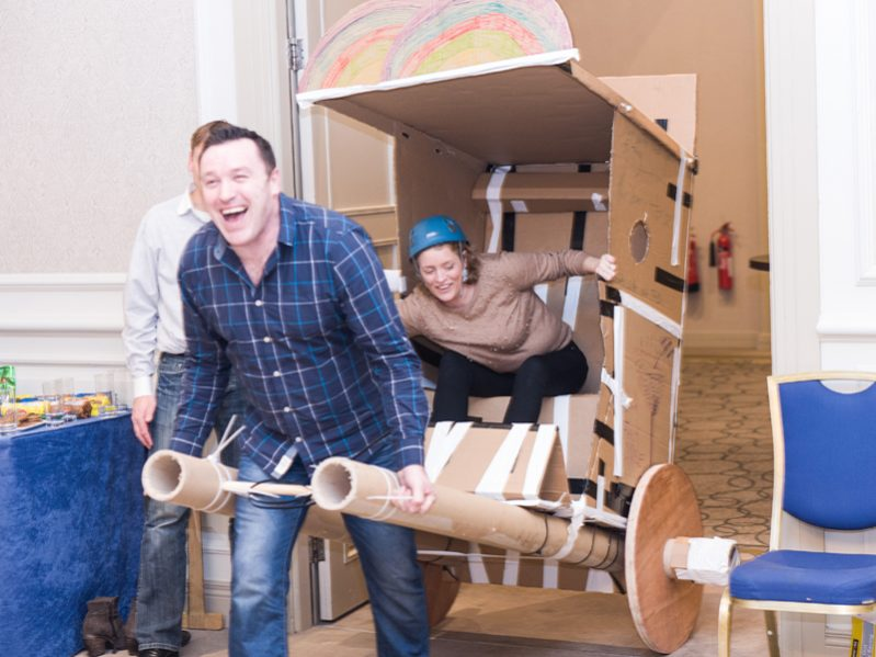 Two delegates getting ready for the final race with the rickshaw they built out of cardboard during their staff away day.