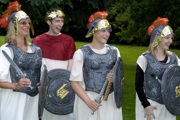 3 delegates dressed as roman soldiers while acting during one of Orangeworks fun, creative team building activities.