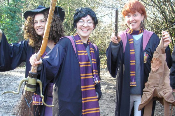 Delegates dressed as Harry, Ron and Hermione smiling for a group photo together during the team activity by Orangeworks.