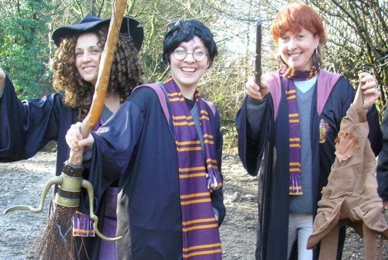 Delegates dressed as Harry, Ron and Hermoine smiling for a group photo together during the team activity by Orangeworks.