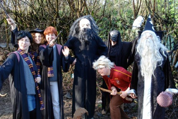 Delegates dressed up as Harry Potter characters smiling for a photo during Fifteen Famous Minutes, the team activity.