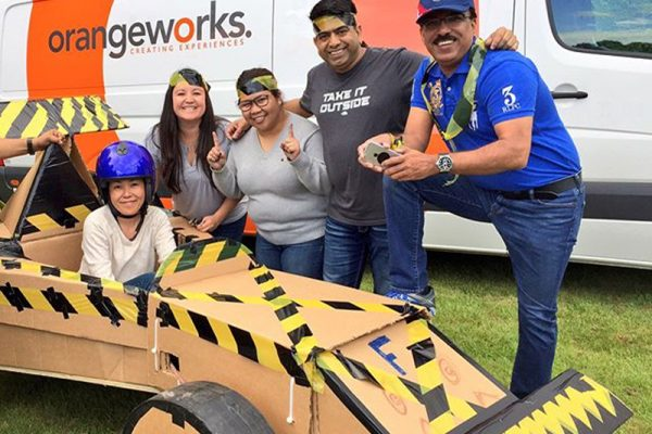 Delegates smiling with their Flat Out Formula 1 car