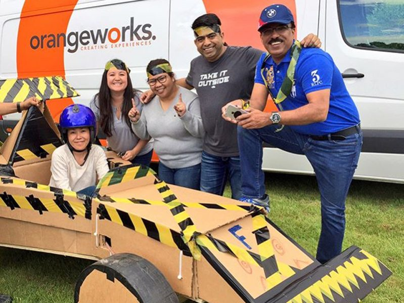 Delegates smiling with their Flat Out Formula 1 car they built and designed during their staff day out with Orangeworks.