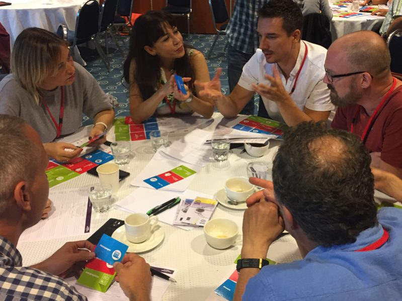 Team discussing their creative ideas during Global Innovation Game, a corporate experience that inspires entrepreneurship.