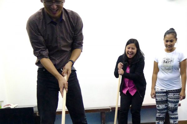Laughing colleagues during Orangeworks mini golf style team bonding activity called Hole in One.