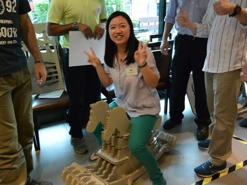 Delegates smiling with the wooden horses they built during their charity based corporate away day hosted by Orangeworks.