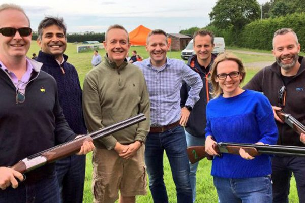 Group smiling before real clay pigeon shooting