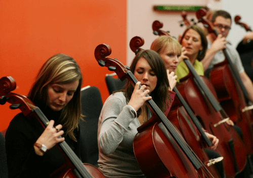 Delegates learning how to play the cello during Orchestrate, a music-themed corporate event by Orangeworks.