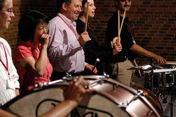 5 delegates holding drumsticks, practising their drumming skills during Orangeworks musical team event Orchestrate.