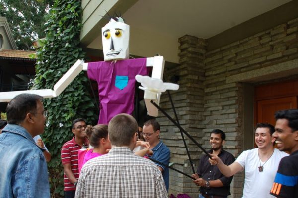 Participants of the creative team challenge Puppet Masters, holding up their puppet as they prepare for the final catwalk.