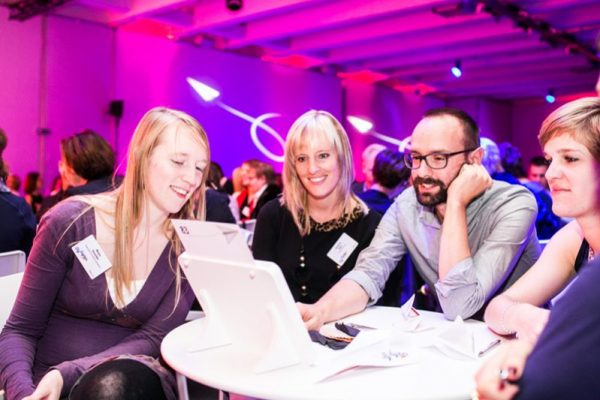 Delegates working together on their next quiz question, during Push It, a corporate evening interaction experience.