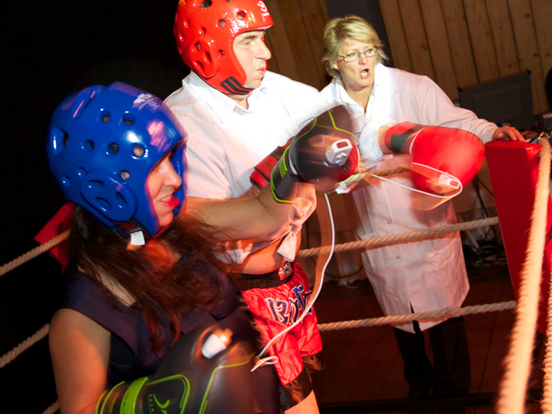 Delegates competing in a Push It boxing game, a high energy team building activity by Orangeworks.