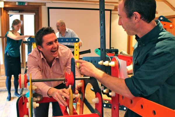 Laughing colleagues building their part of the Rat Trap together, a unique team building activity hosted by Orangeworks.