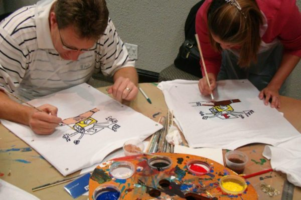 Two delegates of the fun high energy team bonding activity T-shirt Masterpiece painting their team t-shirts together.