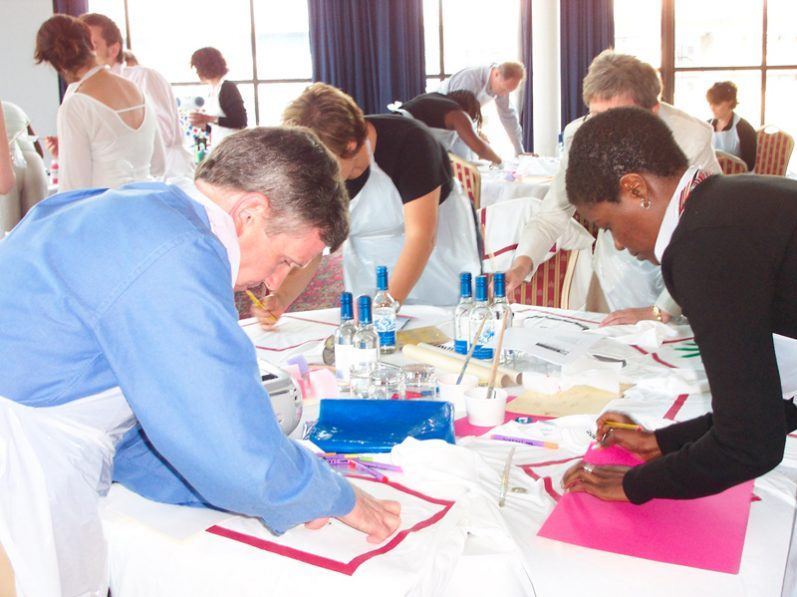 Delegates in the middle of designing their team t-shirts during T-shirt Masterpiece, a corporate team away day event.