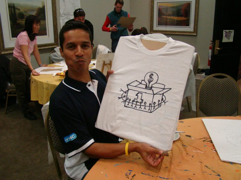 A delegate smiling with their newly designed t-shirt during Tshirt Masterpiece, a staff bonding challenge by Orangeworks.