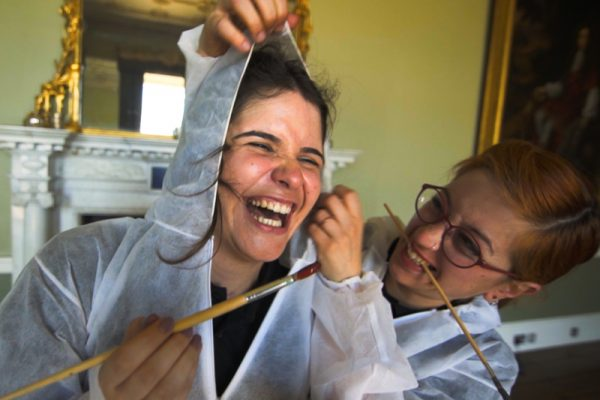 Delegates smiling with paint brushes during Big Picture, a creative team building challenge.