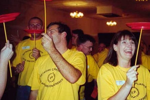 Delegates learning how to balance plates while laughing during Urban Circus with Orangeworks.