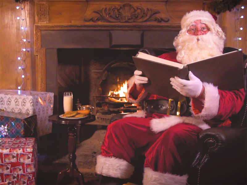 Santa Claus Sitting next to a lit fire reading a book