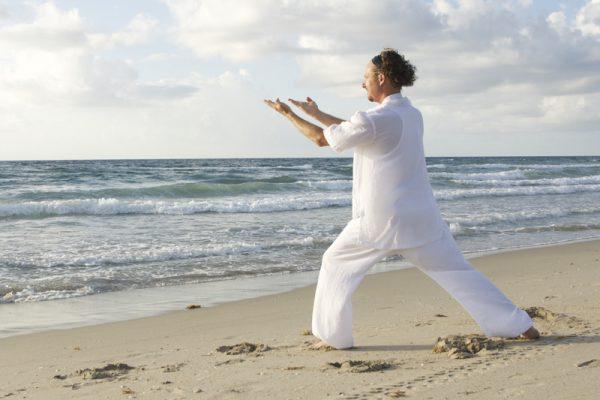Man doing Tai Chi on a beach