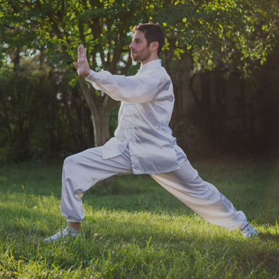 A Tai Chi master doing the warrior posture outside in the grass during a team activity by Orangeworks.