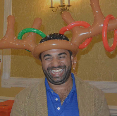 A laughing delegate with inflatable reindeer antlers on his head, having fun during Quickfire Christmas, a corporate event.