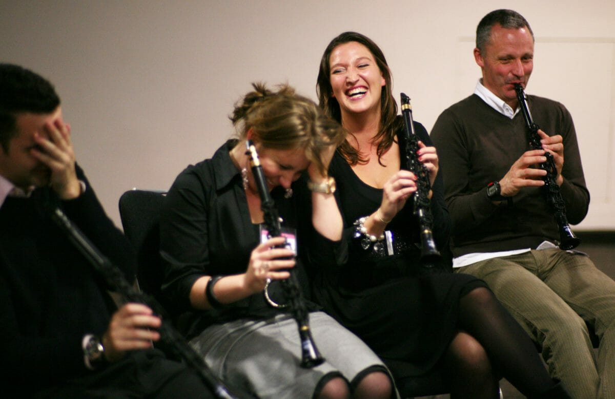 Delegates laughing and learning how to play the clarinet during the music related team building challenge by Orangeworks.