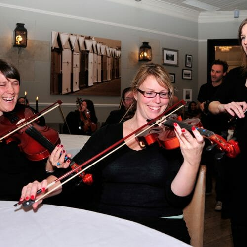 Delegates holding violins and learning how to play then during the music team bonding challenge by Orangeworks