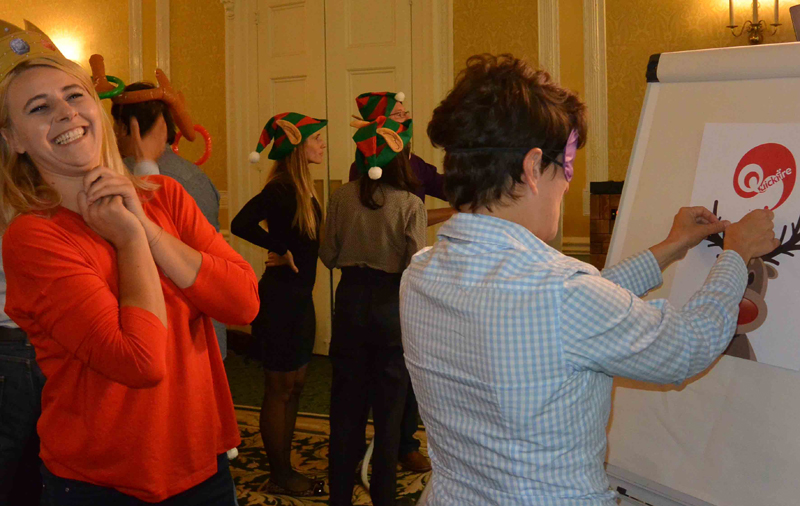 Delegates playing pin the red nose on Rudolph during Quickfire Christmas