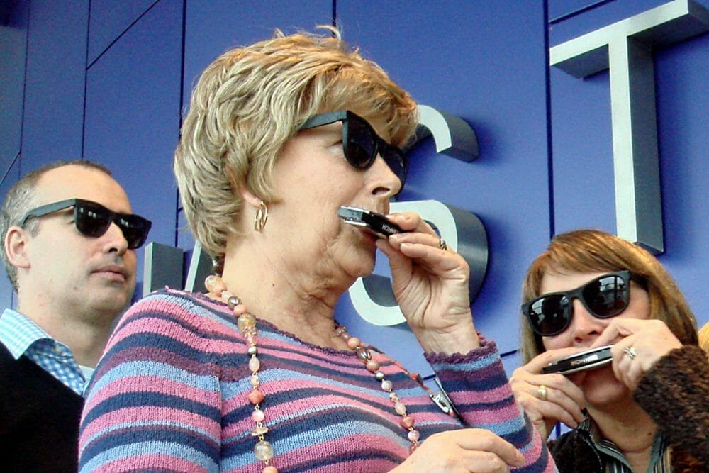 3 delegates playing the harmonicas with sunglasses on during the music-themed team-building exercise Blow the Blues Away.