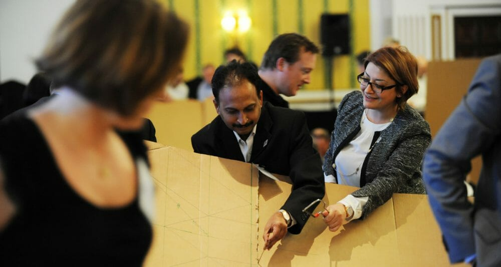 Delegates cutting cardboard during Flat Out Pyramids - a creative team-building activity with Orangeworks