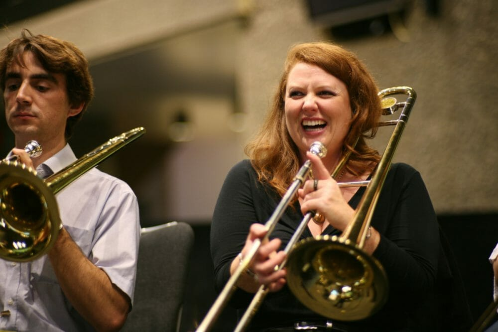 A girl of the team building game Orchestrate holding a trumpet and laughing.