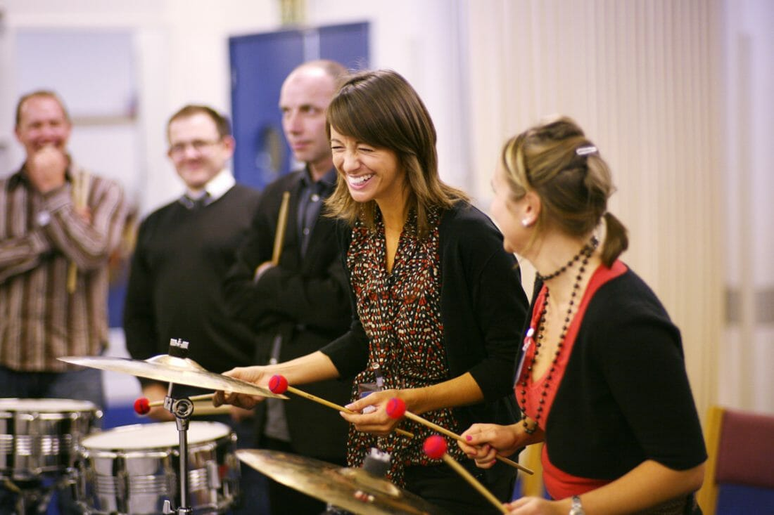 Delegates playing the drums and percussion instruments during their fun team bonding event by Orangeworks