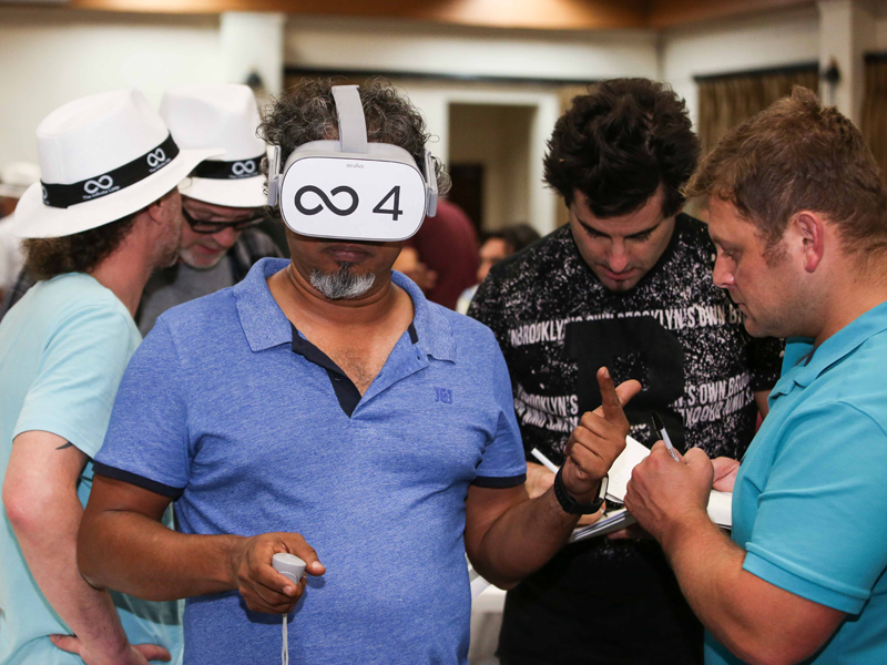 A delegate of Infinite loop, the virtual reality team building game, with a VR headset on and controller in his hand.