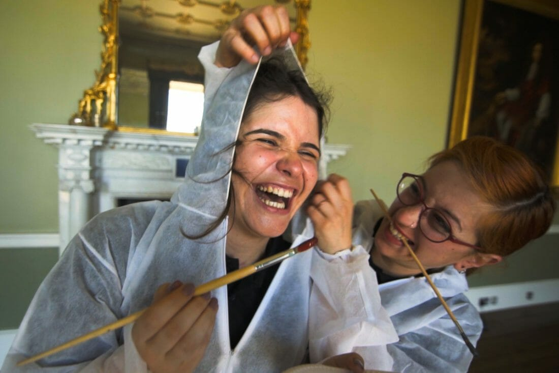 Two delegates of The Big Picture painting, laughing and enjoying their corporate away day team bonding activity.