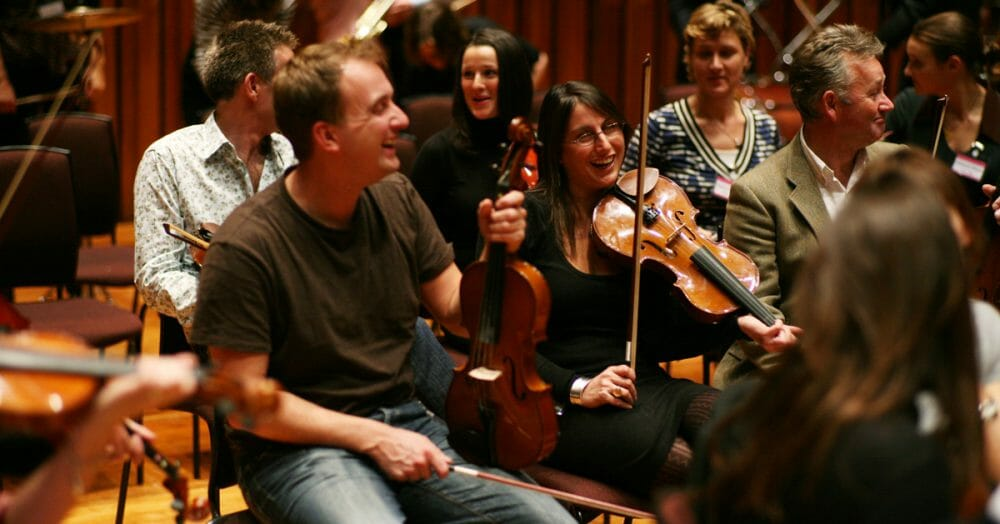 The team holding their instruments and laughing during Orchestrate, a music-themed team building activity by Orangeworks.