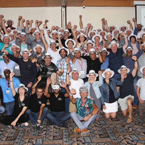 A group of participants of the corporate team exercise called the Infinite Loop raising their hands and smiling