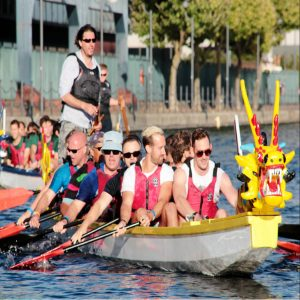 delegates participating in a watersport team building activity called dragon boating.