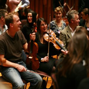 Delegates of the team building activity 'Orchestrate', learning how to play the violin.