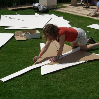 A woman drawing and lining out her cardboard pyramid during Flat out Pyramid, a team bonding exercise by Orangeworks.