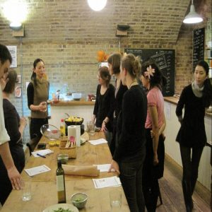 A woman speaking to other women who are taking a Japanese cooking class as part of their team bonding activity in london.