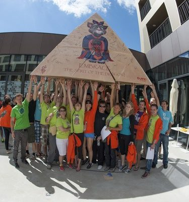 A team of delegates holding up a cardboard pyramid that they made together during Flat Out Pyramid by Orangeworks.