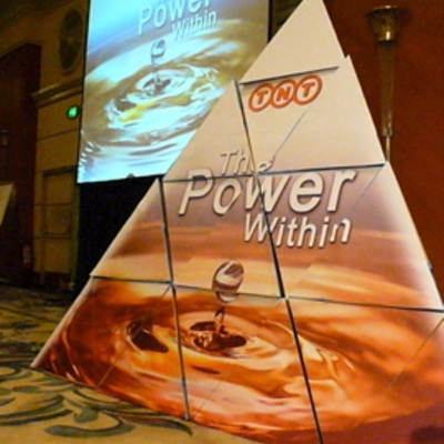 A gigantic cardboard pyramid made of smaller pyramids put together with 'TNT The Power Within' written on them.